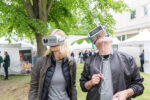 Two visitors of a former Innovation Day are wearing virtual reality glasses