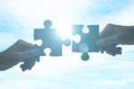 Hands putting puzzle pieces together on sky background with sunlight visualising a partner request from a Research Centre.