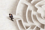 Person standing in front of a labyrinth searching for the right way.