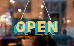 """Sign hanging on a glass door saying """"open"""" to announce the opening of the 28th CORNET Call for Proposals"""