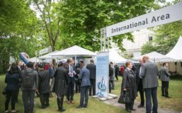 "Big Sign with the letters ""International Area"" is marking the entrance of the International Area at the Innovation Day 2019. Several groups of people are standing on the grass talking."