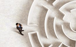 Person standing infront of a labyrinth searching for the right way